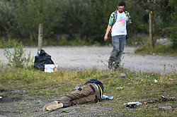 © Licensed to London News Pictures. 30/08/2020. City, UK. A man lies on the floor during an illegal rave in the village of Banwen, south Wales. The event, which was held in forestry above the village was attended by an estimated 3000 people from all over the UK. The government recently strengthened the laws to fine organisers of the illegal parties £10,000. Photo credit: Robert Melen/LNP