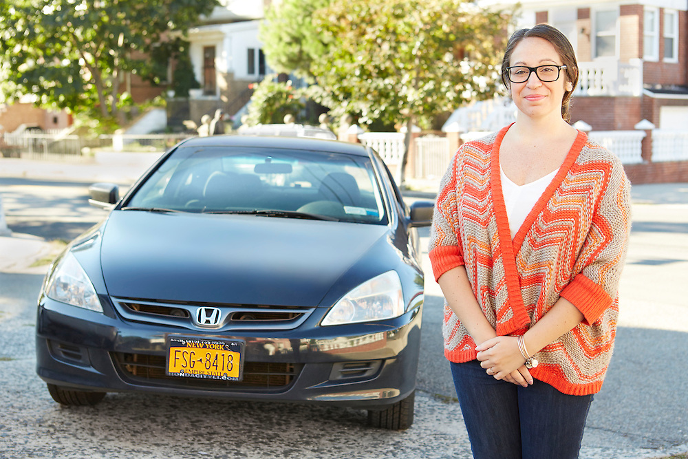 Lifestyle image of young woman standing in front of black Honda car in suburban town