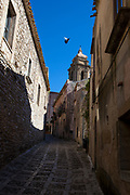 Via dei Normanni, and the Catholic church of Chiesa di San Giuliano. Street view in the ancient city of Erice, Sicily, Italy.