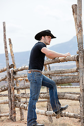 cowboy leaning on a rustic fence outdoors