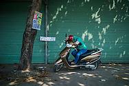 A vietnamese woman takes a nap on her motorbike between Vung Tau and HCMC, Vietnam, Southeast Asia
