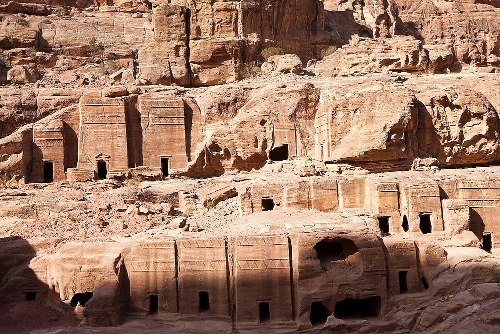 A Bedouin sits in the entrance of a tomb of the Street of Facades in Petra, Jordan.