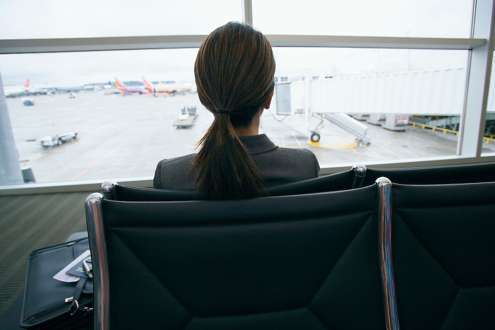 View from behind a dark haired business woman sitting at the airport waiting for her airplane to arrive..20050916_MR_B.20050916_PR_A
