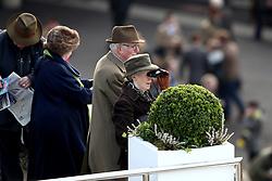 A racegoer views the action using a pair of binoculars during St Patrick's Thursday of the 2018 Cheltenham Festival at Cheltenham Racecourse.