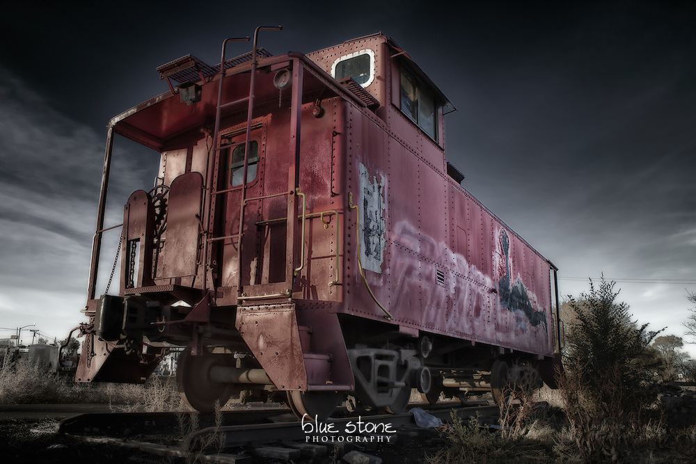 A rail car with faded red paint and graffiti on the side that has been stranded at a modern city intersection.<br /> <br /> Wall art is available in metal, canvas, float wrap and standout. Art prints are available in lustre, glossy, matte and metallic finishes.
