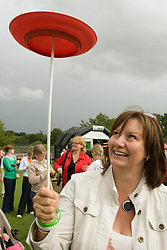 Woman learning to spin a plate during a circus skills workshop at a Parklife summer activities event,
