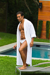 good looking man in a bathrobe by a swimming pool