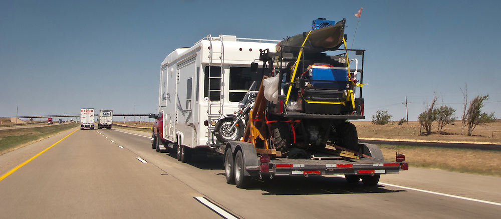 A pickup truck pulls a large travel trailer with slideouts pulling a flatbed trailer with a dunebuggy, motorcycle, canoe and other recreation equipment on rural west Texas Interstate 20. Panorama