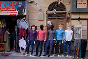 Mannequins in an outside clothing business displaying the latest western-style clothes for males in modern Luxor, Nile Valley, Egypt. The models are leaning in the same direction while the two, far right, are missing their upper torsos.