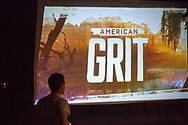"""Merrick, New York, USA. 11th June 2017.  In backyard of """"American Grit"""" contestant Chris Edom, Edom walks up where the American Grit logo appears on large screen that show's premiere episode is projected on in his backyard. Edom family hosted neighborhood Viewing Party during broadcast of Episode 1 of the FOX network reality television series."""