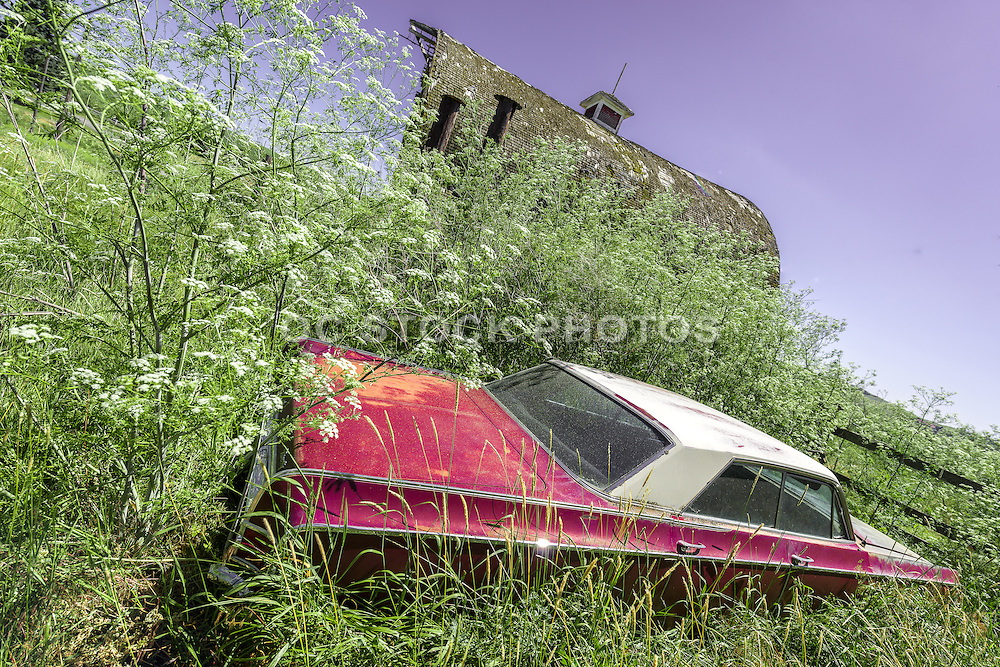 Red Abandoned Car Next to an Old Barn in a Grassy Field