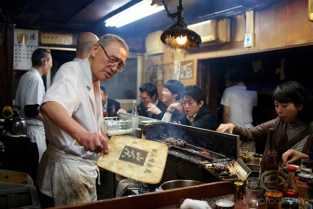 This chef has been working in the same yakitori bar for almost 50 years. The lamp hanging over the grill hasn't changed in decades. The holder, gathering all the smoky fats from the grill, transformed in a sculpture. Shinjuku, Tokyo, Japan.