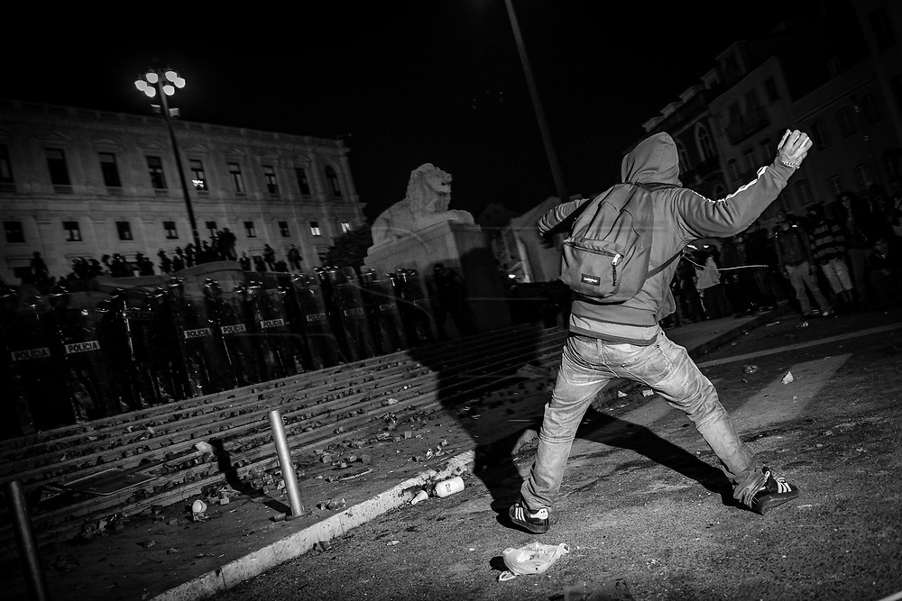 A protester throws stones at Portuguese parliament guarded by riot police in front of the Portuguese parliament during a demonstration against further austerity to be implemented by the government. Portugal is known by it's peaceful revolution that overthrew the fascist dictatorship of Oliveira Salazar in 1974. However, unprecedented violence caused by anger and helplessness is starting to arise in a country where scenes as the one depicted are rare.