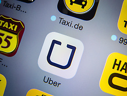 Detail of iPhone screen with Uber mobile app for booking taxis