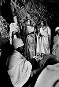 Ethiopian Orthodox pilgrims at Lalibela, Ethiopia. Monks chant their prayers to the accompanied drumming and beating of their prayers sticks in a cave during the festival of Timkat (Epiphany). Lalibela in northern Ethiopia is famous for it's monolithic roack hewn churches and is one Ethiopia's holiest cities and a centre of pilgrimage for much of the country.