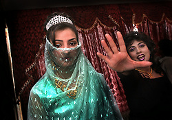 KABUL,AFGHANISTAN - AUGUST 29: An Afghan bride prepares for wedding photos as her sister gestures to  stop so she can look in the mirror first during a wedding ceremony, August 30, 2002 in Kabul, Afghanistan. In Afghan weddings, the bride will first wear a green dress and laer change into a white dress. Each Friday, every beauty salon is filled with  brides, the hotels are jammed with young couples and most streets are packed with streams of cars, blaring their horns as Afghans rush to get married after decades of war. (Photo by Ami Vitale/Getty Images)