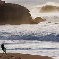 A surfer watches Pacific Ocean waves roll ashore at Montara State Beach, California.