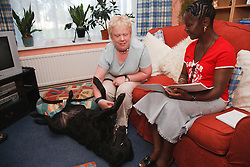 Woman with visual impairment with friend studying in living room.