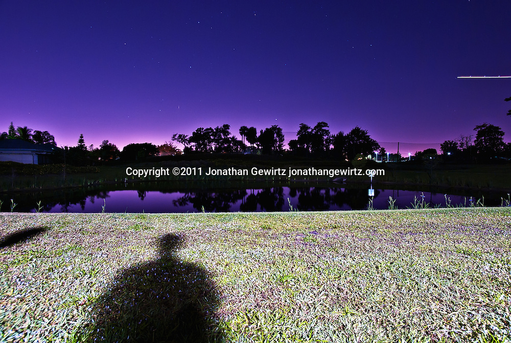Human shadows on a grassy lawn under a purple sky at night. WATERMARKS WILL NOT APPEAR ON PRINTS OR LICENSED IMAGES.