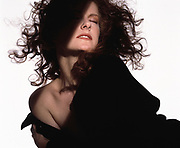 Woman with long wavy curly hair with shaft of light illuminating her face. Black dress falling off and exposing one shoulder
