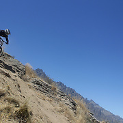 Craig Cox from Queenstown in action during the New Zealand South Island Downhill Cup Mountain Bike series held on The Remarkables face with a stunning backdrop of the Wakatipu Basin. 150 riders took part in the two day event. Queenstown, Otago, New Zealand. 9th January 2012. Photo Tim Clayton