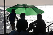 Couple and child with green umbrella silhouette by ocean