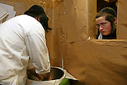 The process of baking unleavened matza bread for Passover begins with the flour mix; the room is kept covered with brown paper for hygienic purposes and the ingredients are totally separate. The baking process from start to finish has to be completed within 18 minutes for it to be Kosher. They are baking matza bread for Passover out the back of Bethune Road synagogue.