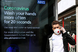 © Licensed to London News Pictures. 09/03/2020. London, UK. A man wearing protective face mask and plastic gloves is seen speaking on the phone next to the Coronavirus public information campaign poster in London, which focuses on hand washing. Three coronavirus victims have died and 278 cases have tested positive for the virus. Photo credit: Dinendra Haria/LNP