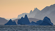 The towering peak of Grundtvigskirken towers above icebergs stranded in O Fjord, as seen from near Syckap, Scoresby Sund, Greenland.