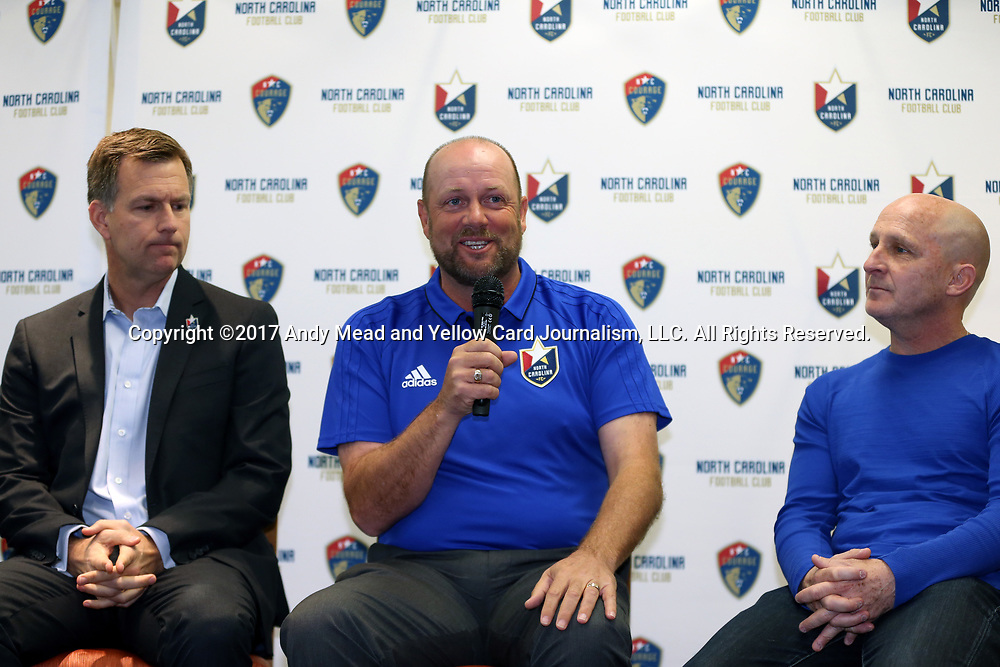 DURHAM, NC - MARCH 20: North Carolina FC head coach Colin Clarke (NIR) (center) answers questions with team president Curt Johnson (left) and North Carolina Courage head coach Paul Riley (right). North Carolina Football Club held their annual media luncheon on March 20, 2017, at Hyatt Place Durham Southpoint in Durham, NC. The press function served as a kickoff to the seasons of the North American Soccer League's North Carolina FC and the National Women's Soccer League's North Carolina Courage professional teams.