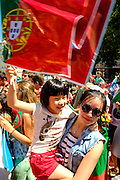 Mother and daughter from the chinese community living in Lisbon celebrating with a portuguese flag the winning of the country's first football Euro Cup. Portugal's national squad won the Euro Cup the day before, beating in the final France, the organizing country of the European Football Championship, in a match that ended 1-0 after extra-time.