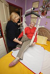 Carer with woman with disability using a hoist.