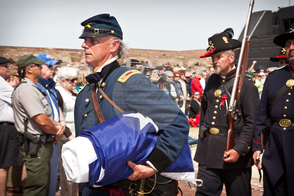 A re-enactor portraying Union officer Maj. Robert Anderson marches out of Fort Sumter with the US Flag on the 150th anniversary of the surrender of the fort in the US Civil War on April 14, 2011 in Charleston, South Carolina.  The surrender of the fort marks the end of a week long commemoration of the start of the Civil War.