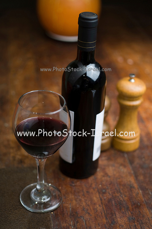 Atmospheric image of a glass and bottle of red wine The bottle has no logo or trademarks and is safe for commercial usage