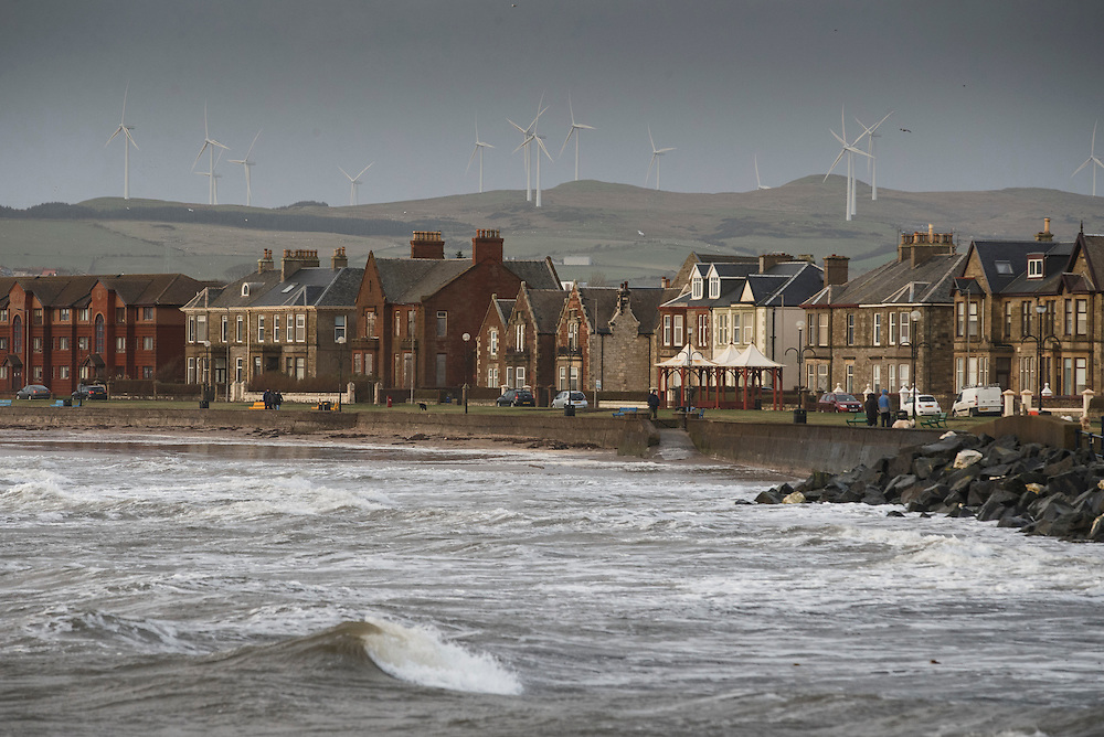 Storm Gertrude. Ayrshire Coast.  The waves batter the coastline at Ardrossan.  A wind farm on the hill. Picture Robert Perry 29th Jan 2016<br /> <br /> Must credit photo to Robert Perry<br /> FEE PAYABLE FOR REPRO USE<br /> FEE PAYABLE FOR ALL INTERNET USE<br /> www.robertperry.co.uk<br /> NB -This image is not to be distributed without the prior consent of the copyright holder.<br /> in using this image you agree to abide by terms and conditions as stated in this caption.<br /> All monies payable to Robert Perry<br /> <br /> (PLEASE DO NOT REMOVE THIS CAPTION)<br /> This image is intended for Editorial use (e.g. news). Any commercial or promotional use requires additional clearance. <br /> Copyright 2014 All rights protected.<br /> first use only<br /> contact details<br /> Robert Perry     <br /> 07702 631 477<br /> robertperryphotos@gmail.com<br /> no internet usage without prior consent.         <br /> Robert Perry reserves the right to pursue unauthorised use of this image . If you violate my intellectual property you may be liable for  damages, loss of income, and profits you derive from the use of this image.