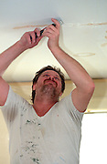 Man age 40 scraping ceiling in preparation for painting.  St Paul  Minnesota USA