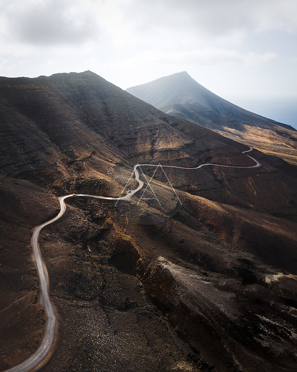 Aerial view of a scenic road driving across the mountain near Cofete, Fuerteventura island, Canary islands, Spain.
