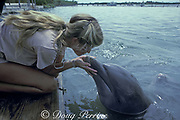 bottlenose dolphin, Tursiops truncatus, gets a kiss from trainer, Dolphin Research Center, Grassy Key, Florida Keys, USA ( Gulf of Mexico )