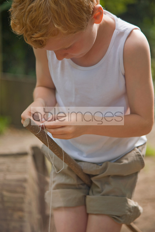 Young boy holding wooden stick between legs tying a knot with a string
