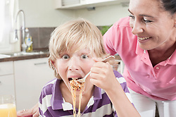 Portrait of a boy eating spaghetti with his mother, Bavaria, Germany