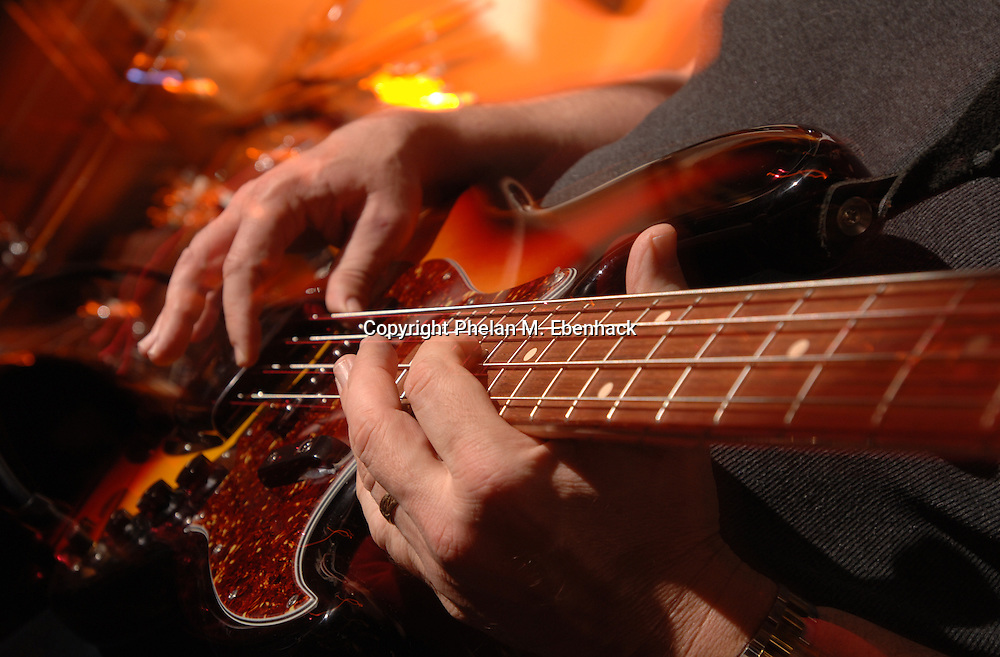 A performer plays a bass guitar during a concert at a bar in Orlando, Florida.