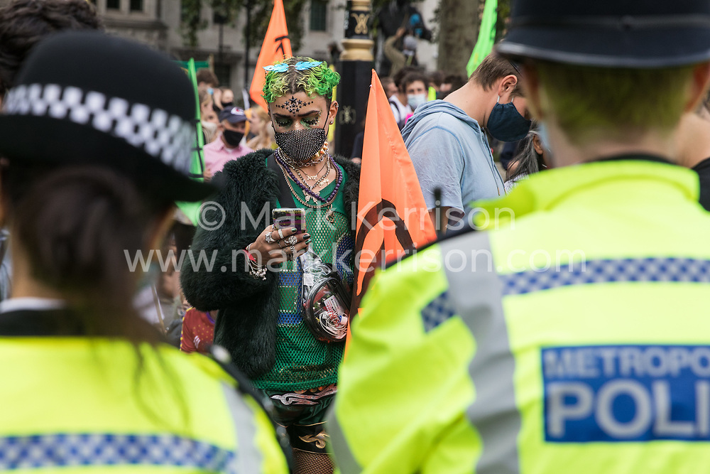 London, UK. 1st September, 2020. Metropolitan Police officers monitor climate activists from Extinction Rebellion occupying roads around Parliament Square during a Back The Bill rally. Extinction Rebellion activists are attending a series of September Rebellion protests around the UK to call on politicians to back the Climate and Ecological Emergency Bill (CEE Bill) which requires, among other measures, a serious plan to deal with the UK's share of emissions and to halt critical rises in global temperatures and for ordinary people to be involved in future environmental planning by means of a Citizens' Assembly.