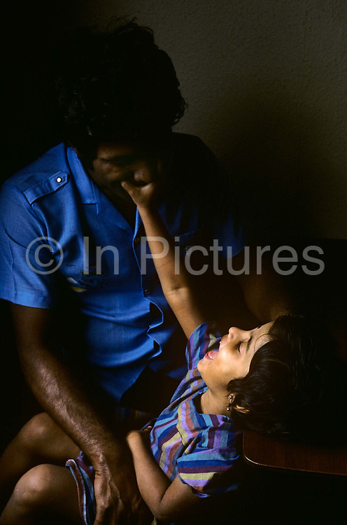A young girl of approximately 9 years of age plays with her father. With window light falling across the dad and girl, the two are both dressed in shades of blue - the father with darker skin than his daughter. They are both Tamil refugees from the Indian Ocean Island of Sri Lanka and have escaped the civil war there where their ethnic group is being dangerously persecuted by the Singhalese majority. The family have recently arrived in Britain seeking political asylum and are temporarily housed in a bare council flat in Chalk Farm in North London. The girl reaches up to touch the man's moustache and he lets her grab his mouth in a playful respite from their life-changing circumstances.