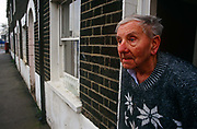 An elderly gentleman looks out from his urban cottage opposite the new Millennium Dome, soon to force him from home. 76 year-old Ronald White stands in the doorway of his home in the short row of Georgian cottages called Ceylon Place that he has lived in for many years. But the construction of the nearby Millennium Dome means that Ronald will have to leave his house and be displaced for the sake of this highly controversial building project, in time for its opening on Millennium night 1999. He looks worried and anxious about his impending move though it is not known if he was ever allowed to move back.