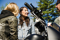 Iron Lilies Leticia Cline and Kissa Von Adams talk with Rob Nadeau before taking off from Laconia Harley Davidson for their group ride up through the Kancamagus Highway on Tuesday morning.   (Karen Bobotas/for the Laconia Daily Sun)