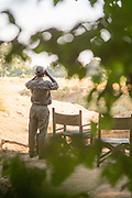 Guide looking through binoculars and chairs at Chikoko Tree Camp, South Luangwa National Park, Zambia