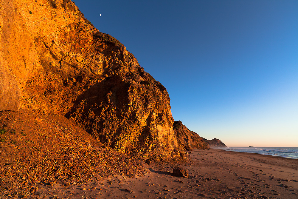 The orange glow of sunset amplifies the colors on the cliffs above Limantour Beach.