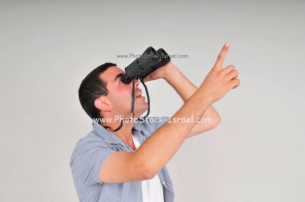 Young man in his early 20s looking through a binoculars