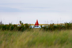 Sailing through Morston Marshes, North Norfolk Coast, England, UK.
