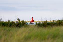 Sailing through Morston Marshes, North Norfolk Coast, England, UK.